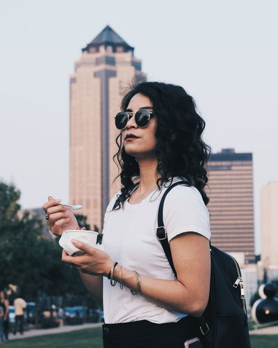 Woman having food while standing against buildings in city