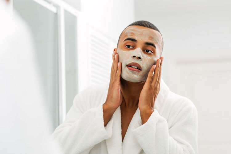 Man applying moisturizer on face while standing at bathroom