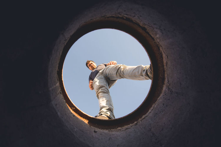 Directly below shot of man seen through hole against sky