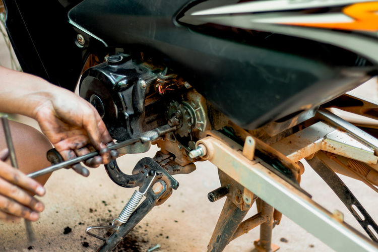 Midsection of man repairing motorcycle