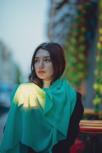 Thoughtful beautiful woman holding glowing jar under blue scarf in city at dusk