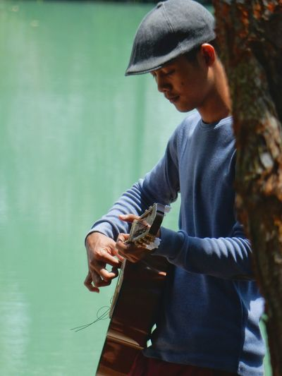 Side view of young man playing guitar