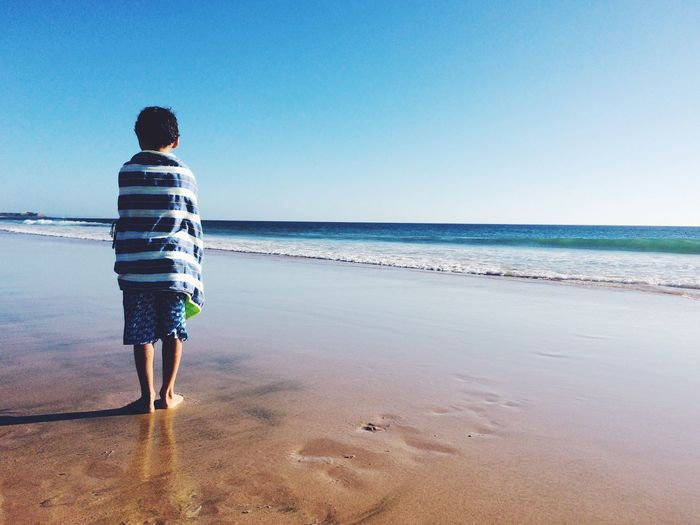 Rear View Of Boy Wrapped In Towel Standing On Shore At Beach Against Clear Sky