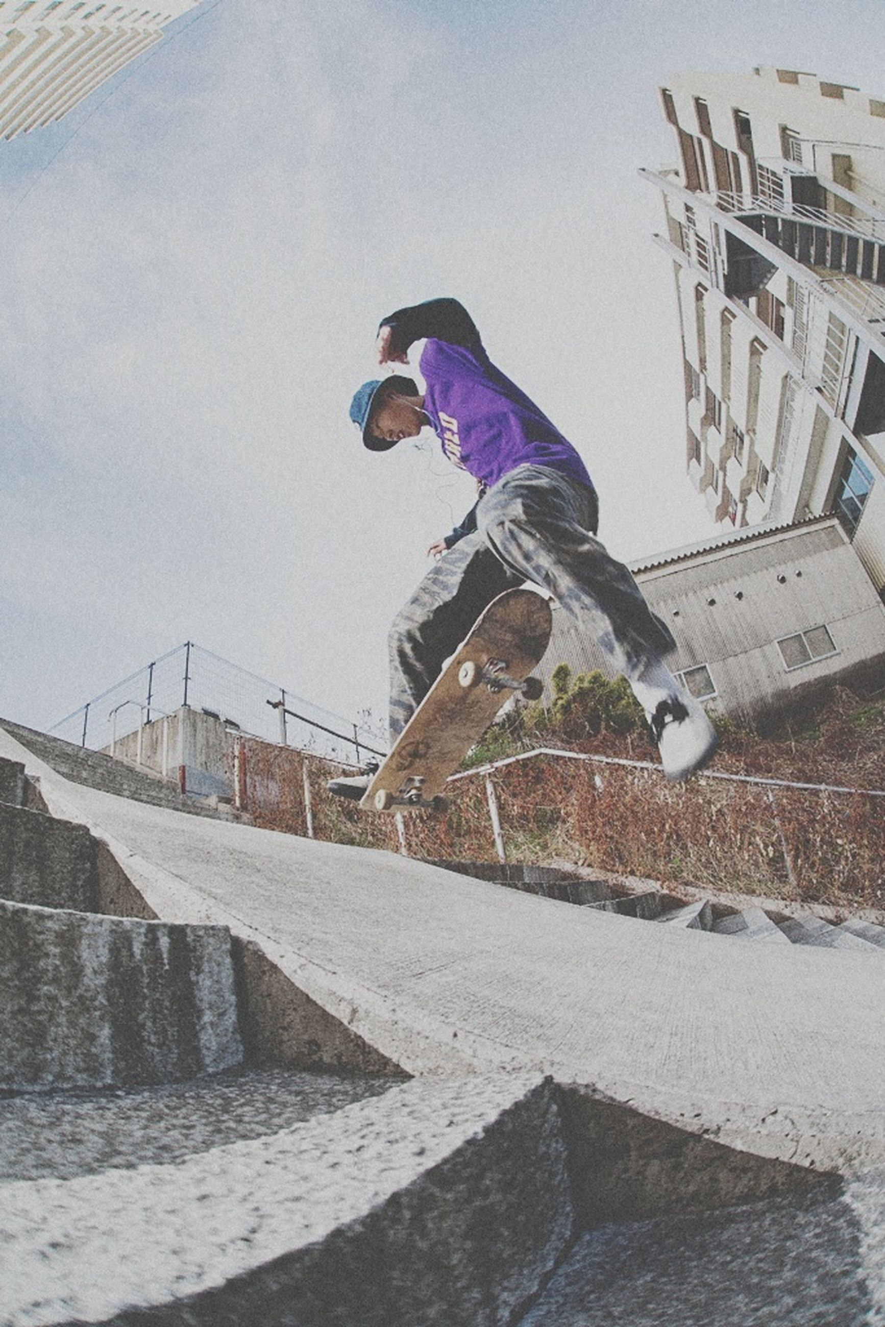 leisure activity, mid-air, full length, real people, lifestyles, jumping, one person, skateboard, skill, motion, sport, stunt, extreme sports, casual clothing, sports ramp, activity, fun, skateboard park, architecture, vitality, outdoors, built structure, young adult, balance, energetic, risk, building exterior, enjoyment, day, men, youth culture, city, sky, people, adult