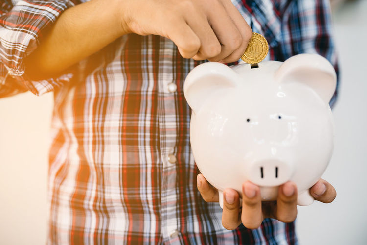 Midsection of man inserting coin in piggy bank