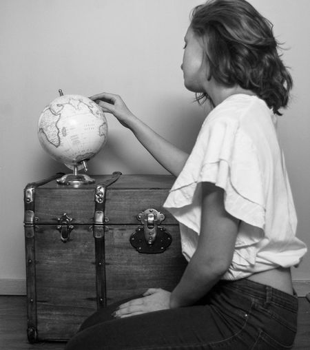 Side view of young woman holding globe on luggage at home