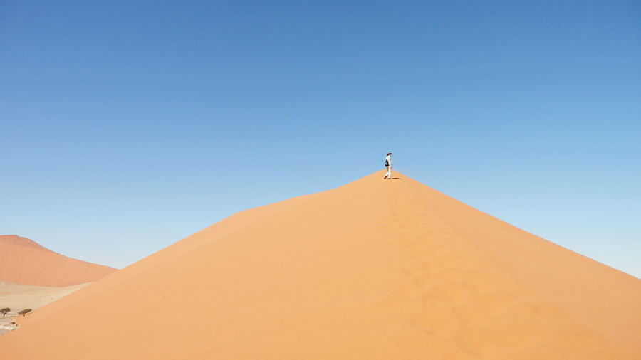 Low angle view of person standing on sand dune at namib desert