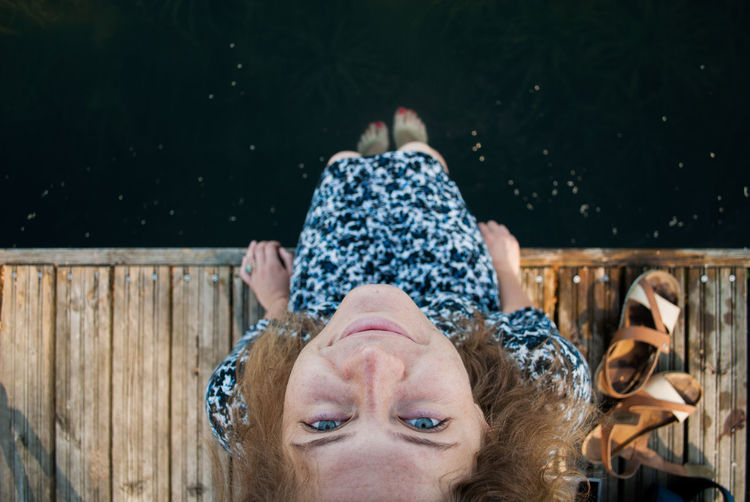 Directly above shot of woman sitting on pier over lake