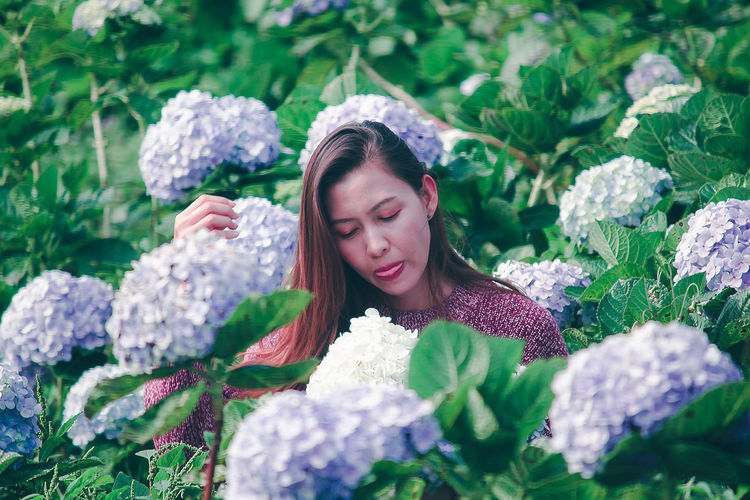 Young woman with flower petals on plants