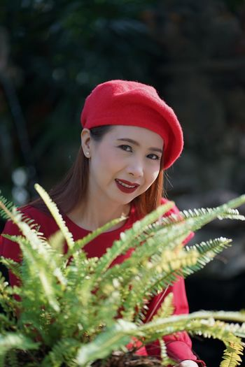 Portrait of beautiful woman wearing hat standing by plants