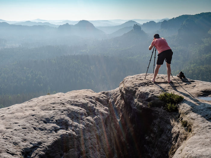 Man looking into viewfinder of his big camera, taking photo of amazing day in hilly landscape