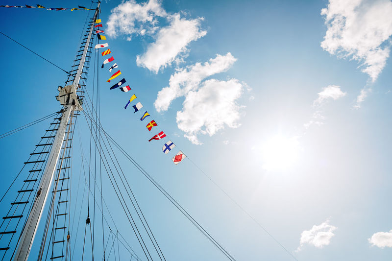 Low angle view of flags hanging against sky