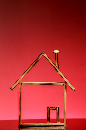 Close-Up Of Wooden Model Home Against Red Background