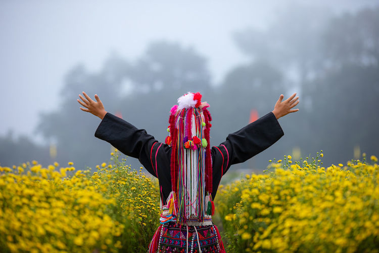 Woman in traditional clothing with arms outstretched standing against trees