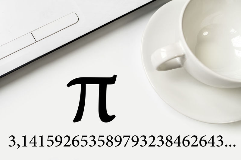 International Pi Day. On a white table a laptop and a cup. Large text and numbers. Close-up Day Indoors  No People Pi Day White Background