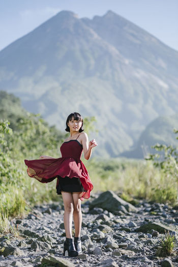 Full length portrait of woman standing on rocks against mountain