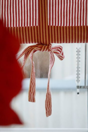 Striped window curtain hanging at home