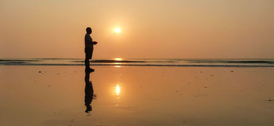 Silhouette man standing on beach during sunset