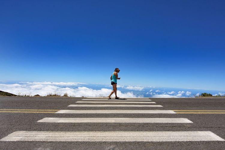 Woman walking on highway at haleakala against blue sky