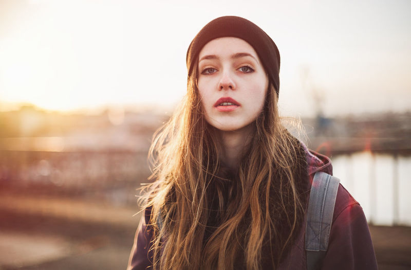 Portrait of a hipster woman at sunset City Student Adult Backpack Beautiful Woman Casual Clothing Clothing Focus On Foreground Front View Hair Hairstyle Headshot Hipster Long Hair Looking At Camera One Person Outdoors Portrait Sky Sunset Teen Teenage Girls Teenager Young Adult Young Women