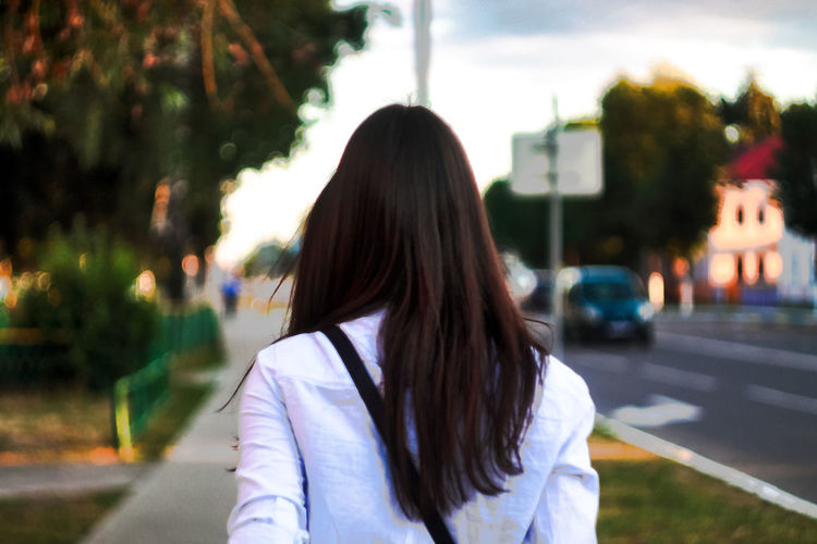 Rear view of woman with long hair walking on sidewalk