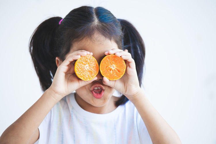 Close-up of girl holding orange slices against white background