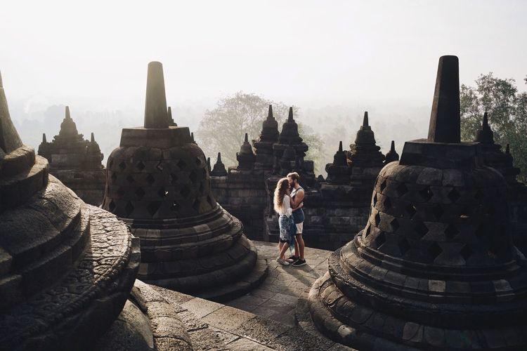 Couple kissing while standing amidst stupas at borobudur