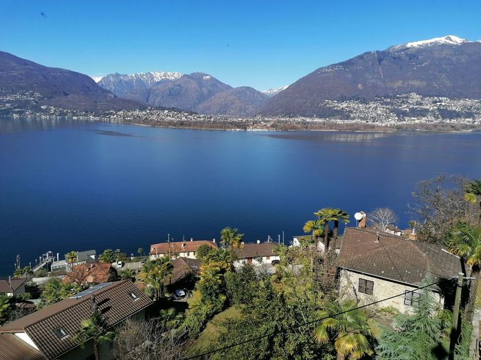 High angle view of townscape by lake against blue sky