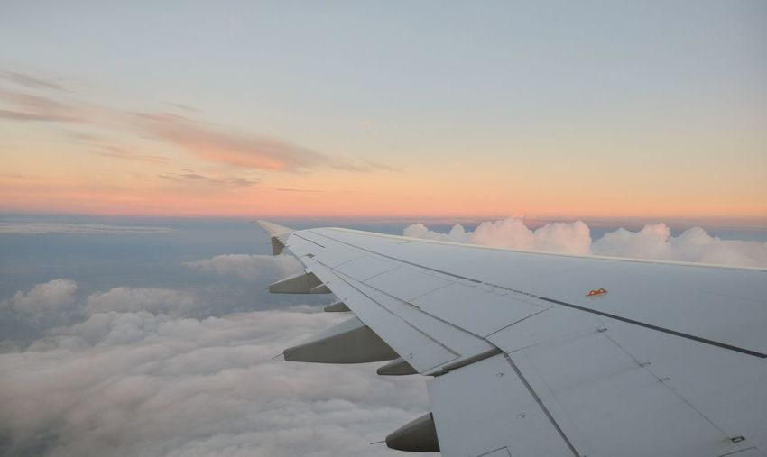 Airplane wing over cloudscape against sky