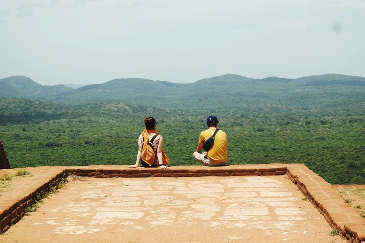 Rear view of friends sitting on retaining wall overlooking green mountains