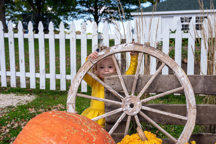 Portrait of girl standing by wheel outdoors