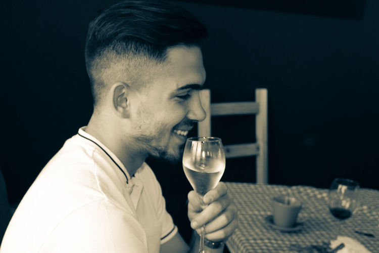Side View Of Smiling Young Man Having Wine At Table In Restaurant