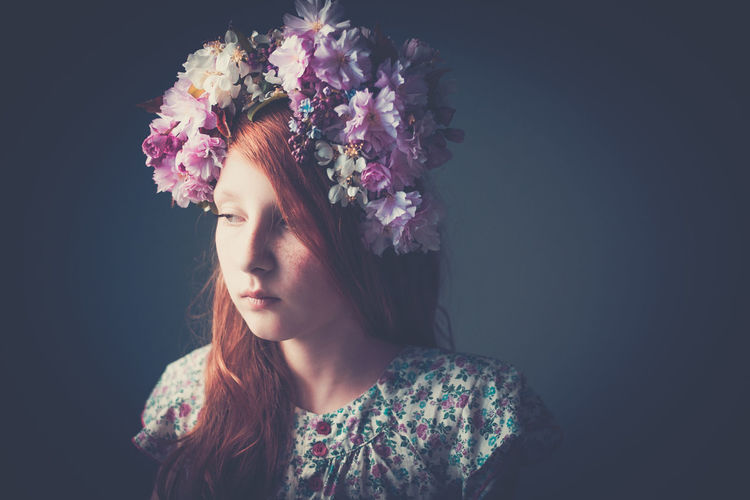 Portrait Of Beautiful Girl And Flowers Against Black Background