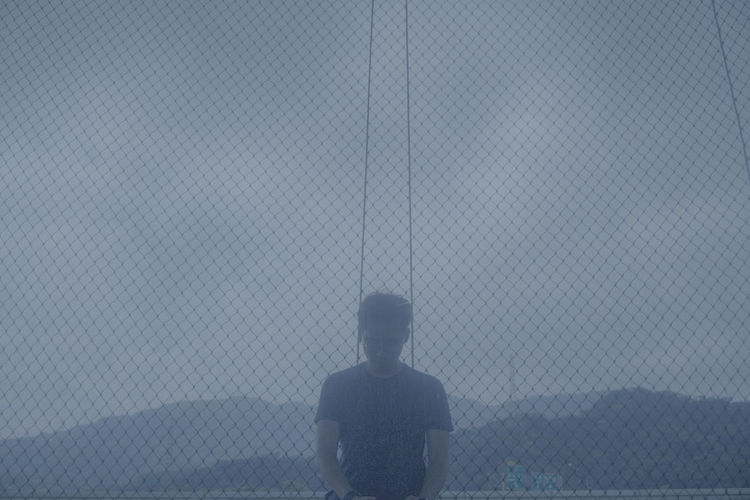 Rear view of man standing against fence