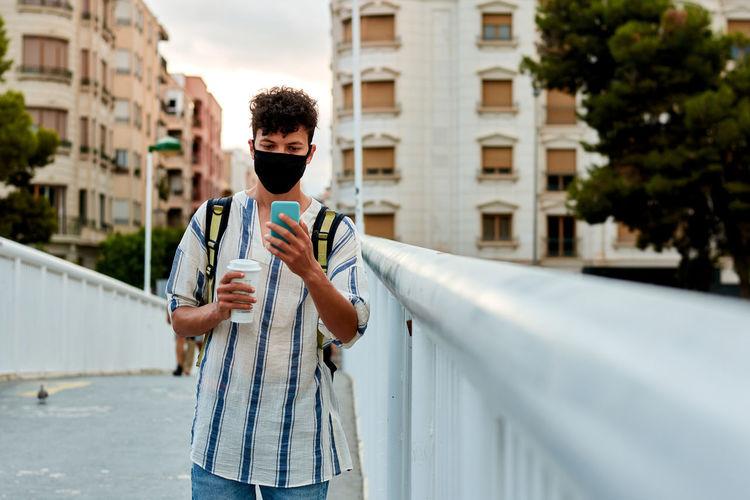 Man holding umbrella standing in city