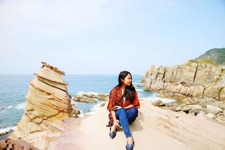 Young woman on rock by sea against sky