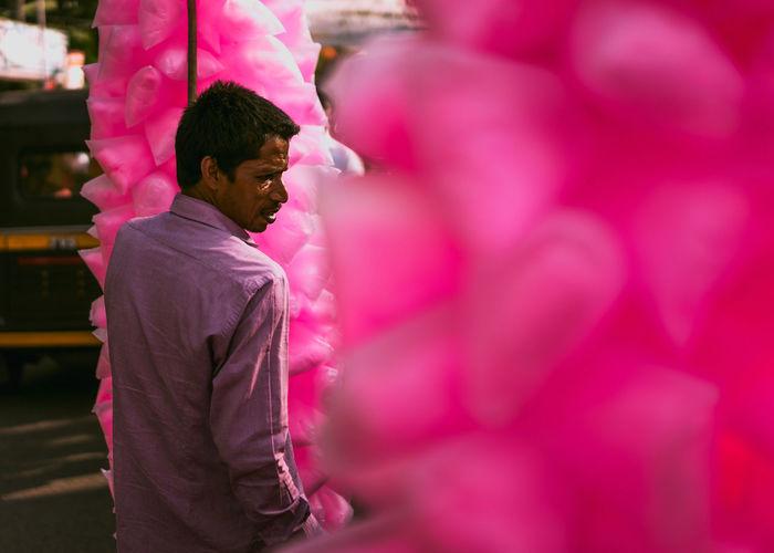 Full length of man standing on pink flower