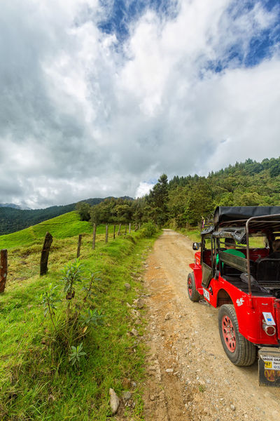 SALENTO, COLOMBIA - JUNE 7: A red jeep parked near pastures in the mountains outside of Salento, Colombia on June 7, 2016. Cloud Colombia Farm Hiking Palm Pasture Quindío Red Rural Tree Trip Andean Cauca Colombian  Countryside Forest Hike Jeep Landscape Quindío Salento Tolima Transportation Trek Wax