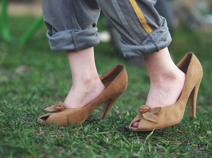 Low section of girl wearing oversized high heels on grassy field