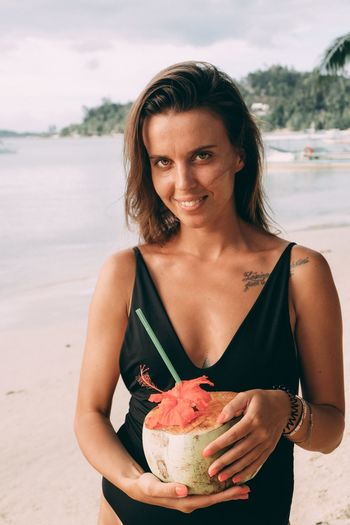 Portrait Of Smiling Woman Holding Coconut At Beach