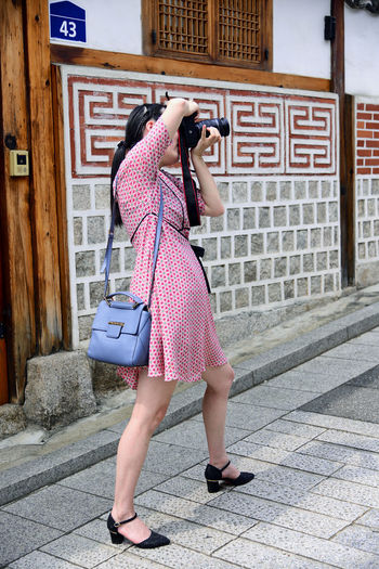 young woman walking on the street One Person Real People Women Architecture Built Structure Lifestyles Building Exterior Full Length Bag Rear View Street Leisure Activity City Holding Footpath Technology Communication Day Adult Outdoors Hairstyle