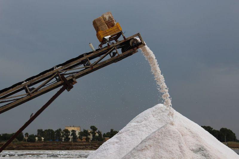 Salt falling from crane against sky