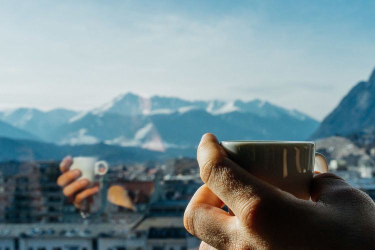 Cropped hand holding coffee cup at glass window