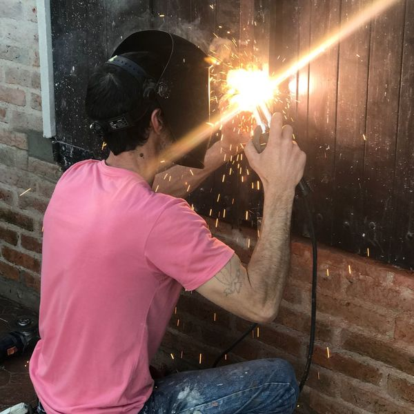 Hard work Welder Man Welder One Person Adult Holding Real People Night City Architecture Casual Clothing Lifestyles Building Exterior Rear View Built Structure Three Quarter Length Motion Technology Sparks