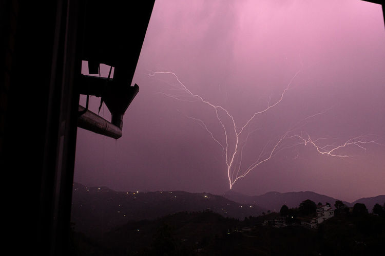Low angle view of lightning in sky over city at night