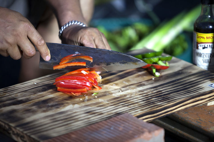 Barbeque Bell Pepper Chef Close-up Cooking Cool Cropped Cutting Board Cutting Vegetables Delicious Focus On Foreground Food Freshness Holding Human Finger Indulgence Knife Lifestyles Midsection Outdoors Part Of Person Selective Focus Unrecognizable Person Vegetable