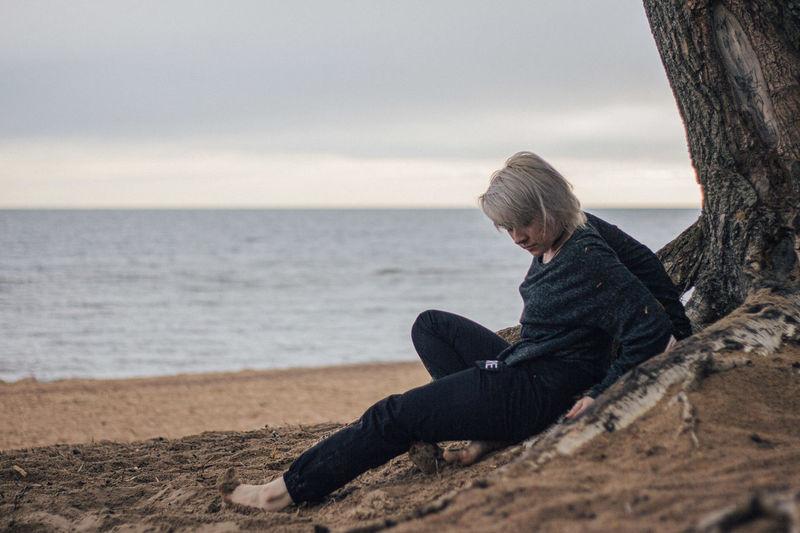 Rear view of boy sitting on beach