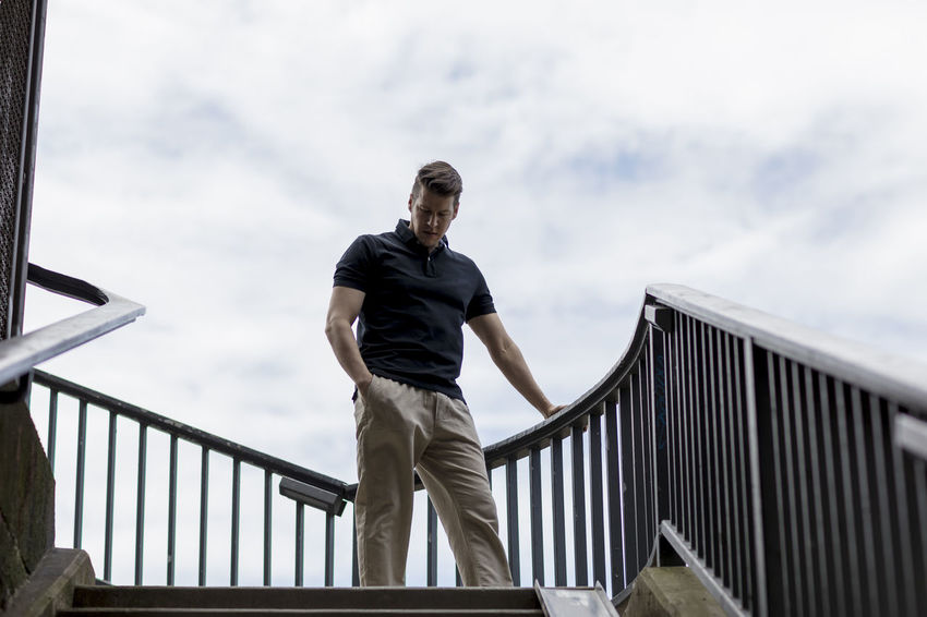 Handsome man dressed casually standing in an outdoor stairwell with one hand in his pocket. Adult Balustrade Cloudy Khaki Pants Long Shot Man Stairs Standing Casual Clothing Caucasian Day Golf Shirt Good Looking Hand In Pocket Handrail  Handsome Head Down Low Angle Model Outside Sky Stairwell Stairwells Summer Walking