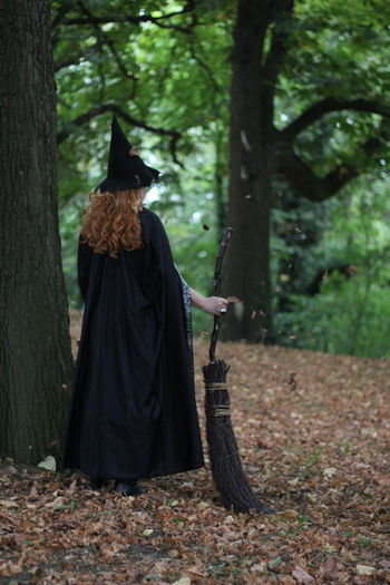 witch holding broom standing in forest