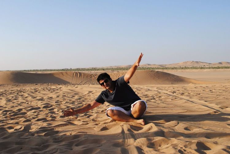 Young man with arms outstretched sitting on sand at desert